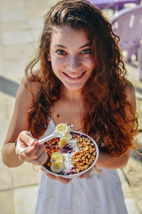 Acai吃早晨早餐的碗妇女在咖啡馆 果子圆滑的人健康饮食特写镜头减重的用莓果和燕麦粥 免版税图库摄影
