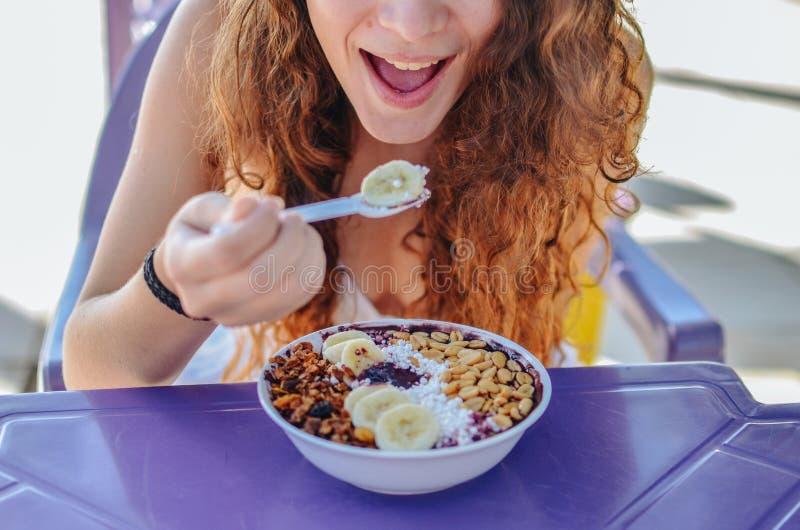 Acai吃早晨早餐的碗妇女在咖啡馆 果子圆滑的人健康饮食特写镜头减重的用莓果和燕麦粥 库存图片