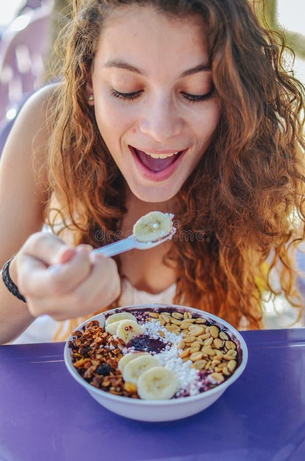 Acai吃早晨早餐的碗妇女在咖啡馆 果子圆滑的人健康饮食特写镜头减重的用莓果和燕麦粥 免版税库存图片