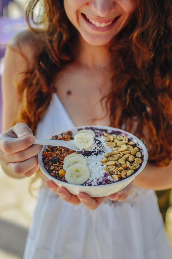 Acai吃早晨早餐的碗妇女在咖啡馆 果子圆滑的人健康饮食特写镜头减重的用莓果和燕麦粥 图库摄影
