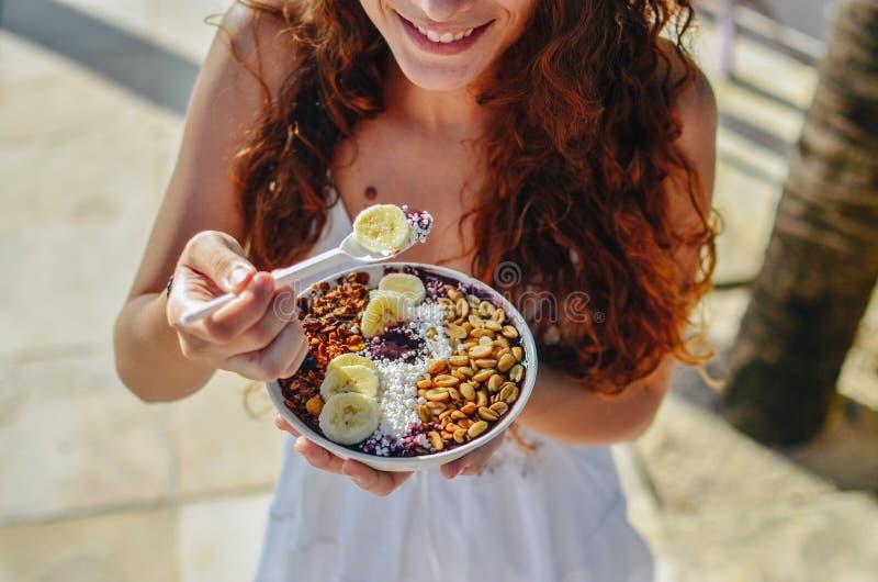 Acai吃早晨早餐的碗妇女在咖啡馆 果子圆滑的人健康饮食特写镜头减重的用莓果和燕麦粥 库存照片