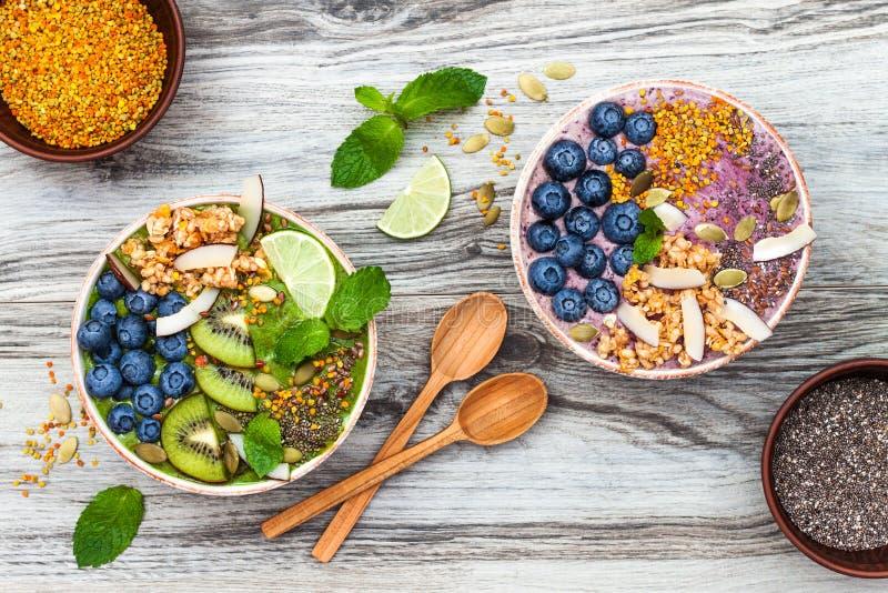 Acai和matcha绿茶早餐superfoods圆滑的人碗冠上了与chia、胡麻和南瓜籽,蜂花粉,格兰诺拉麦片 免版税库存图片