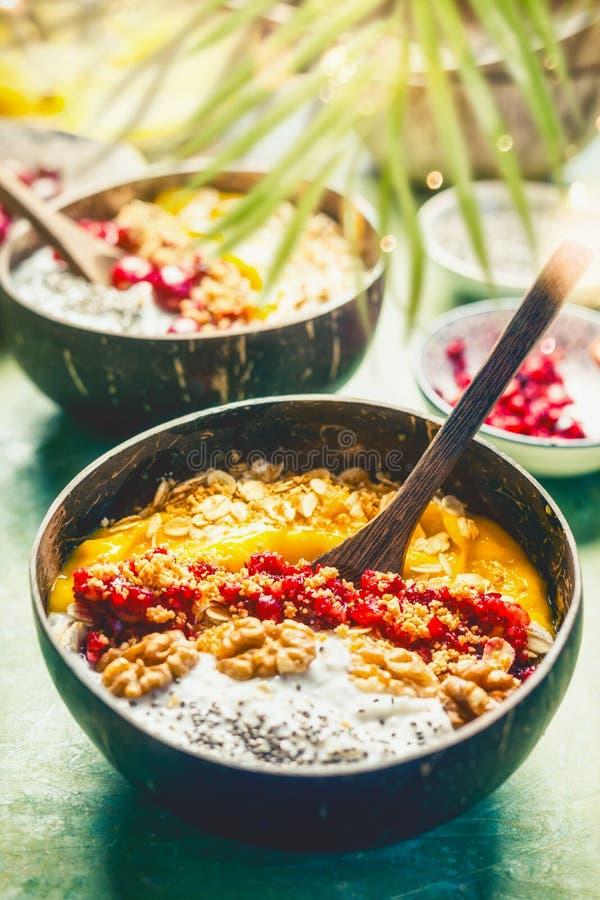 Acai圆滑的人芒果碗用chia种子酸奶布丁和蔓越桔,坚果,冠上在与匙子,上面的椰子壳的燕麦粥 库存照片