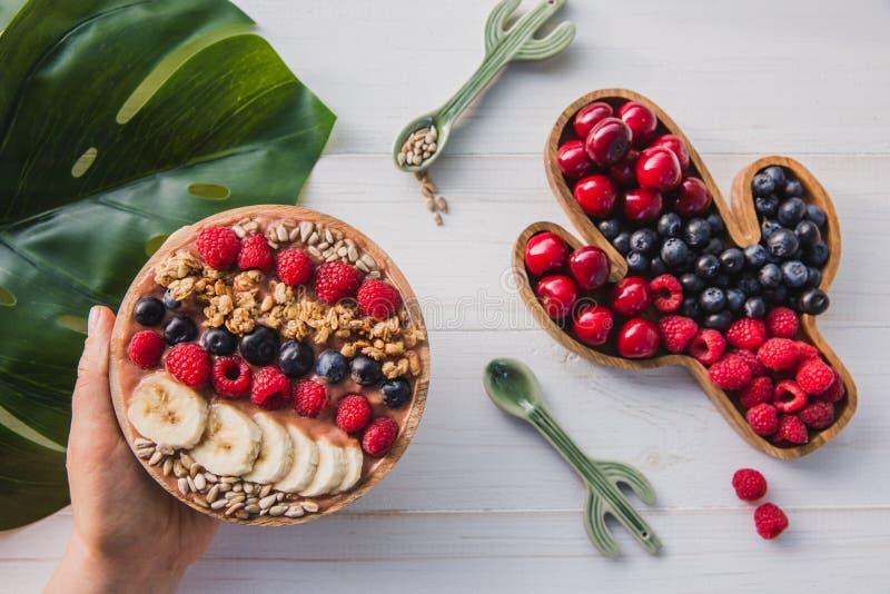 Acai圆滑的人,格兰诺拉麦片,种子,在一个木碗的新鲜水果在有仙人掌匙子的女性手上 板材充满 免版税库存图片
