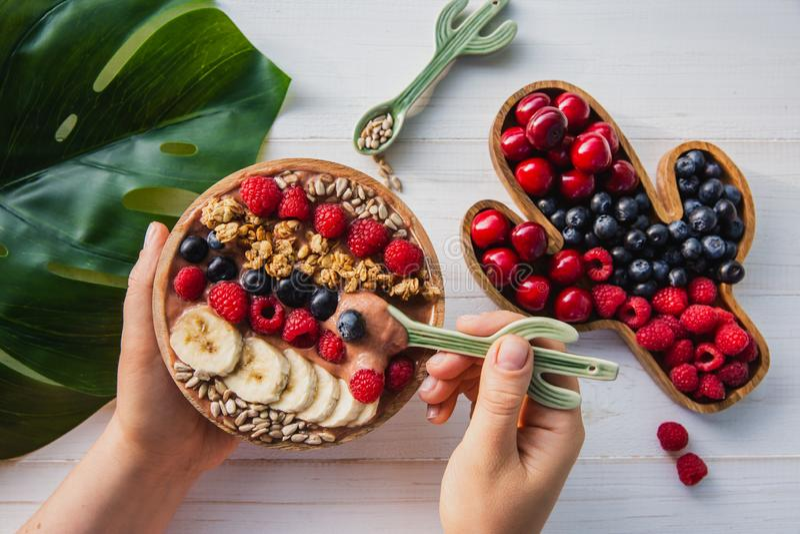Acai圆滑的人,格兰诺拉麦片,种子,在一个木碗的新鲜水果在有仙人掌匙子的女性手上 板材充满 图库摄影
