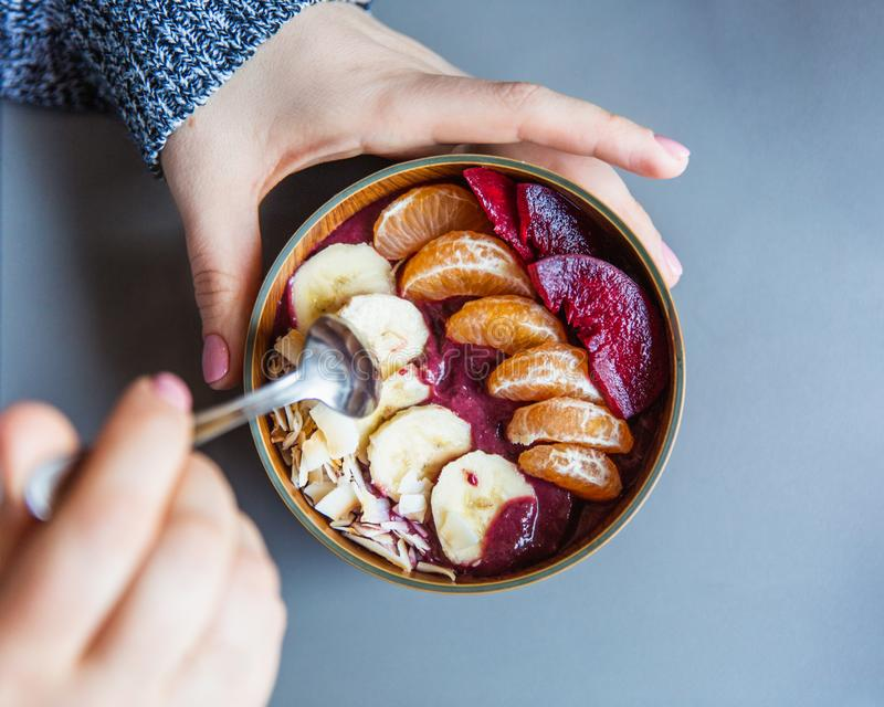 Acai圆滑的人,格兰诺拉麦片,种子,在一个木碗的新鲜水果在灰色桌上的女性手上 吃健康早餐碗 顶层 库存照片
