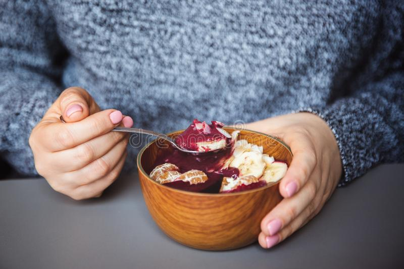 Acai圆滑的人,格兰诺拉麦片,种子,在一个木碗的新鲜水果在灰色桌上的女性手上 吃健康早餐碗 库存图片