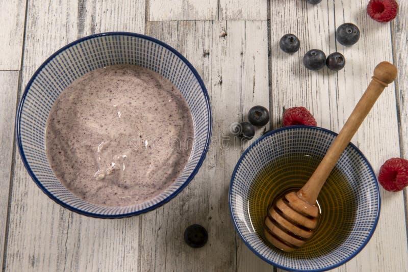Acai碗用莓、蓝莓和一个罐蜂蜜 库存照片