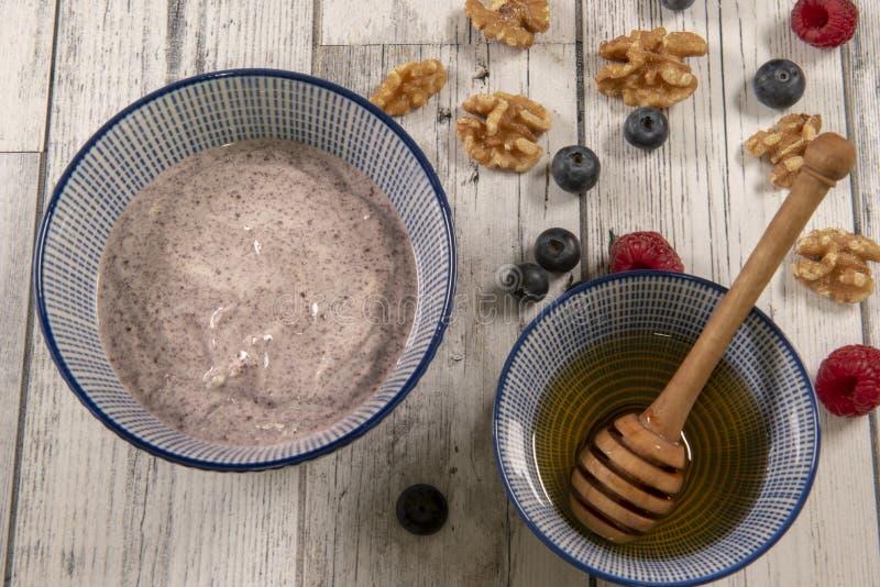 Acai bowl with honey, fresh raspberries and blueberries stock photos
