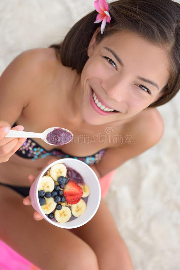 Acai bowl - woman eating healthy food on beach. Girl enjoy acai bowls made from acai berries and fruits outdoors on beach for breakfast. Girl on Hawaii eating stock photo