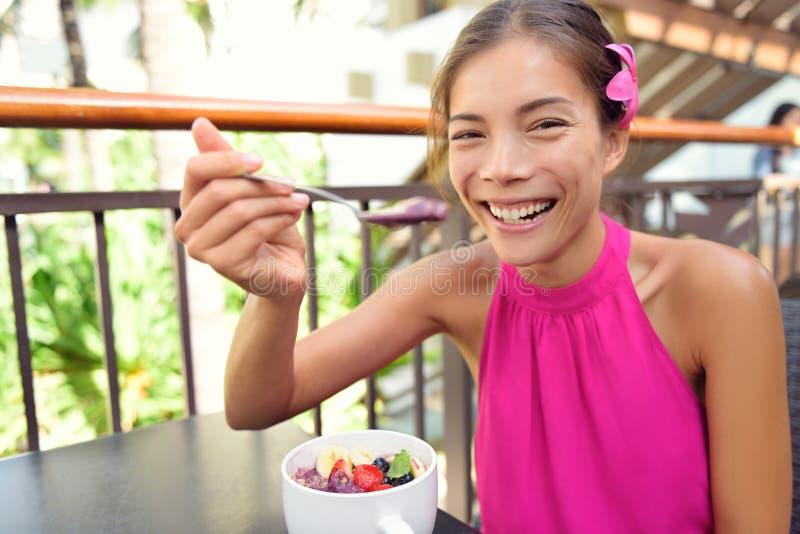 Acai bowl - woman eating healthy food happy. Acai bowl - woman eating healthy food smiling happy. Girl enjoy acai bowls made from acai berries and fruits stock photos