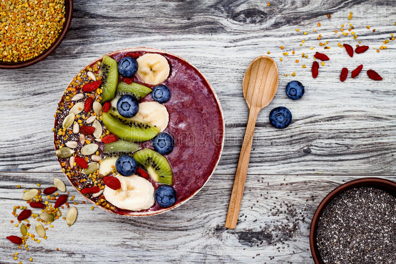 Acai breakfast superfoods smoothies bowl with chia seeds, bee pollen, goji berry toppings and fruits. Overhead. top view, flat lay. Acai breakfast superfoods stock photo