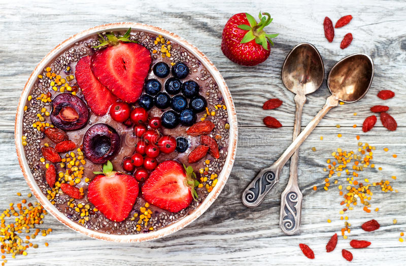 Acai breakfast superfoods smoothies bowl with chia seeds, bee pollen, goji berry toppings and peanut butter. Overhead. Top view stock image