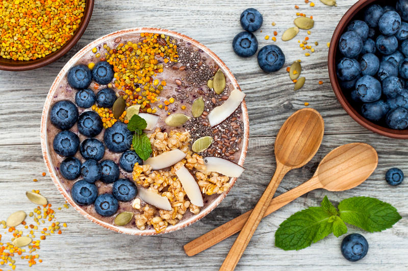 Acai breakfast superfoods smoothies bowl topped with chia, flax and pumpkin seeds, bee pollen, granola, coconut and blueberries. Acai breakfast superfoods stock image