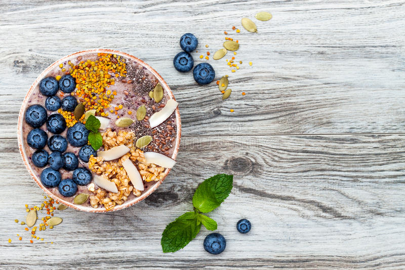 Acai breakfast superfoods smoothies bowl topped with chia, flax and pumpkin seeds, bee pollen, granola, coconut and blueberries stock photo
