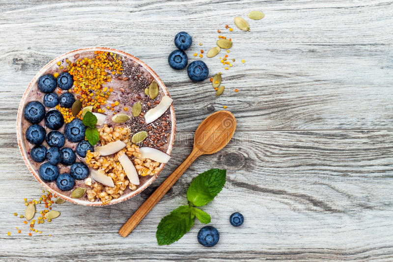 Acai breakfast superfoods smoothies bowl topped with chia, flax and pumpkin seeds, bee pollen, granola, coconut and blueberries stock photos