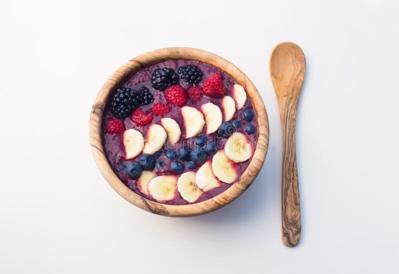 Acai jagodowy smoothie w drewnianym pucharze nakrywającym z bananami, czarnymi jagodami, malinkami i czernicami, obrazy stock