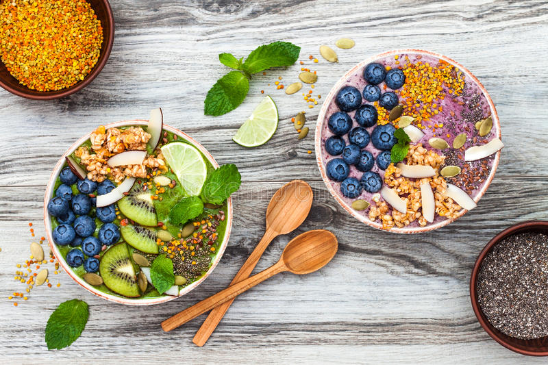 Acai and matcha green tea breakfast superfoods smoothies bowls topped with chia, flax and pumpkin seeds, bee pollen, granola. Coconut flakes and blueberries royalty free stock image