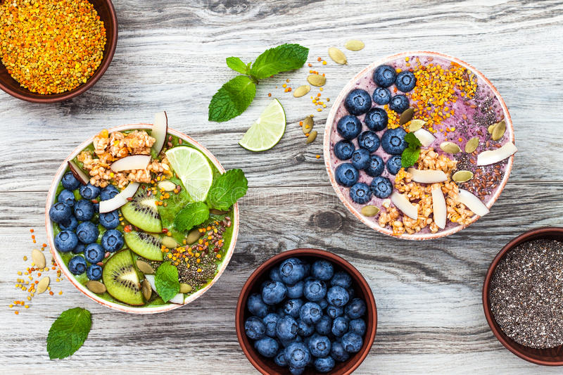 Acai and matcha green tea breakfast superfoods smoothies bowls topped with chia, flax and pumpkin seeds, bee pollen, granola. Coconut flakes and blueberries stock photos