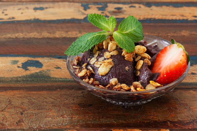 Acai pulp in glass with strawberry, muesli and fresh mint on woo royalty free stock photography
