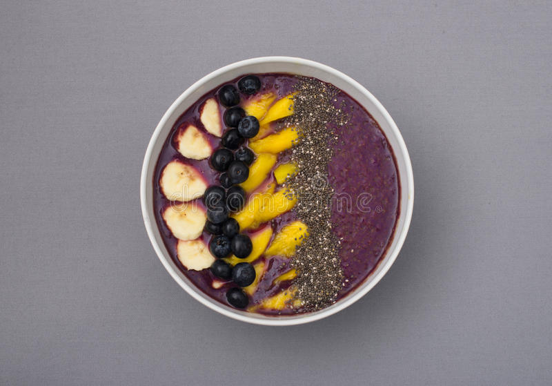 Acai smoothie bowl topped with chia seeds, mango slices, blueberries and bananas royalty free stock images