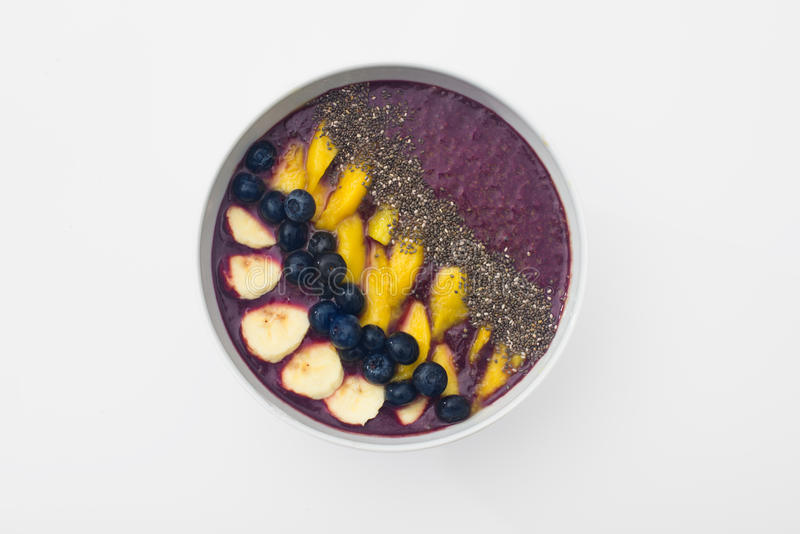 Acai smoothie bowl topped with chia seeds, mango slices, blueberries and bananas stock images