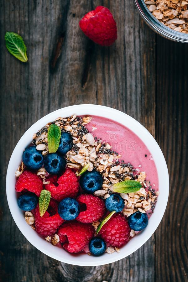 Acai smoothie and granola bowl with fresh raspberries and blueberries. On wooden background royalty free stock photo