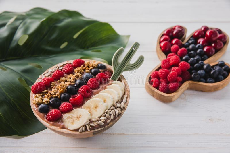 Acai smoothie, granola, frö, nya frukter i en träbunke med kaktusskeden Platta som fylls med bär på vit arkivfoton