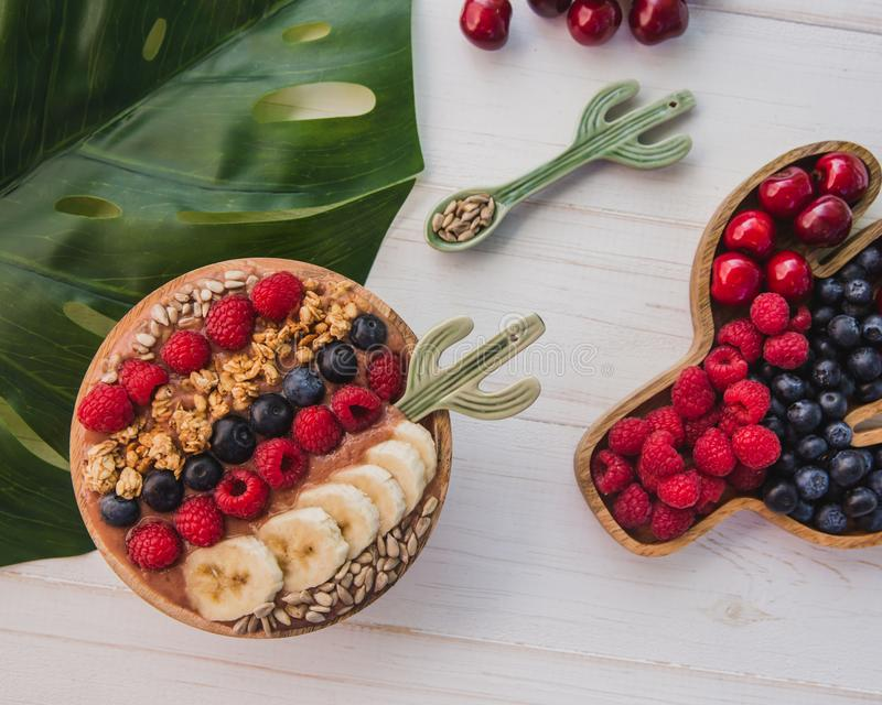Acai smoothie, granola, seeds, fresh fruits in a wooden bowl with cactus spoon. Plate filled with berries on white stock images