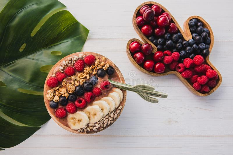 Acai smoothie, granola, seeds, fresh fruits in a wooden bowl with cactus spoon. Plate filled with berries on white stock image