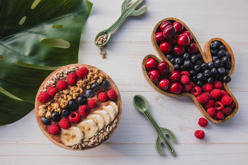 Acai smoothie, granola, seeds, fresh fruits in a wooden bowl with cactus spoon. Plate filled with berries on white royalty free stock photography
