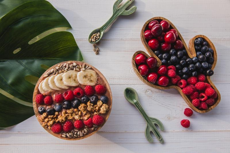 Acai smoothie, granola, seeds, fresh fruits in a wooden bowl with cactus spoon. Plate filled with berries on white stock photography