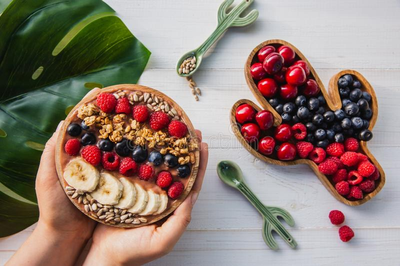 Acai smoothie, granola, seeds, fresh fruits in a wooden bowl in female hands with cactus spoon. Plate filled with royalty free stock image