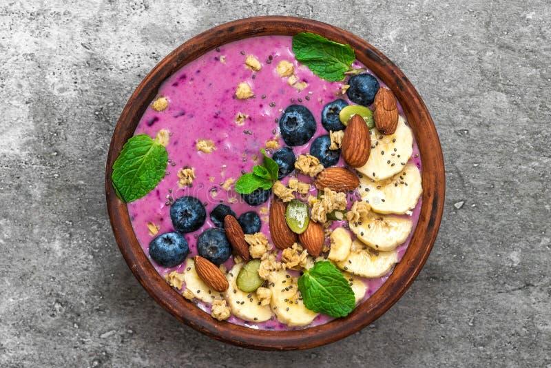 Acai smoothie werpt bedekt met banaan, chia en pompoenzaad, bosbes, amandelen en granola Gezond veganistontbijt royalty-vrije stock foto's
