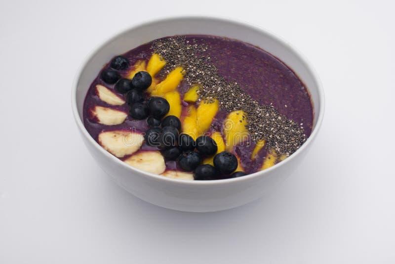 Acai smoothiebunke som överträffas med chiafrö, mangoskivor, blåbär och bananer arkivfoton