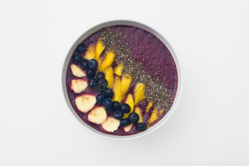 Acai smoothiebunke som överträffas med chiafrö, mangoskivor, blåbär och bananer arkivbilder