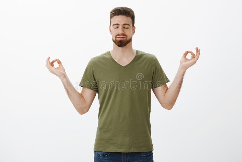 Acalmando para baixo e liberando o esforço com meditação Indivíduo farpado atrativo determinado e relaxado no t-shirt verde-oliva fotos de stock