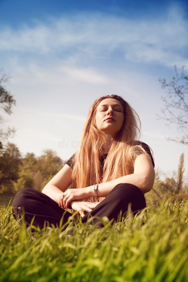 Acalme a mulher que relaxa no campo de grama ensolarado foto de stock