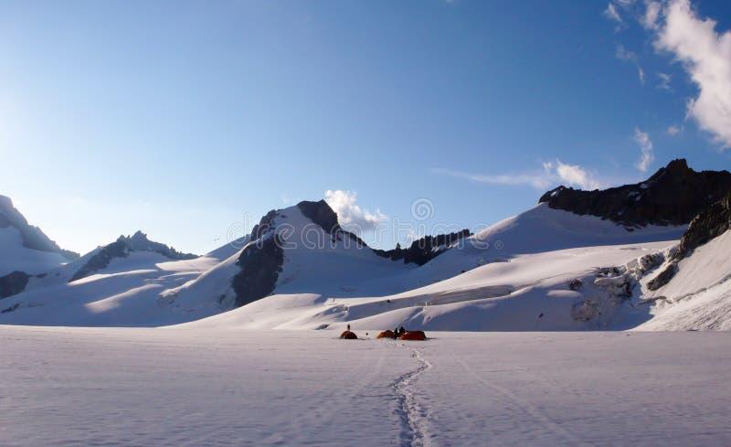 Acampamento base com muitas barracas em uma geleira alpina alta nos cumes perto de Chamonix fotos de stock royalty free