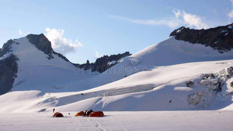 Acampamento base com muitas barracas em uma geleira alpina alta nos cumes perto de Chamonix foto de stock