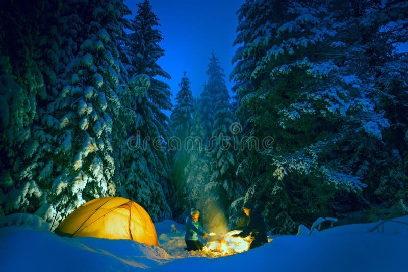 Acampamento com ar livre da fogueira e da barraca no inverno fotos de stock