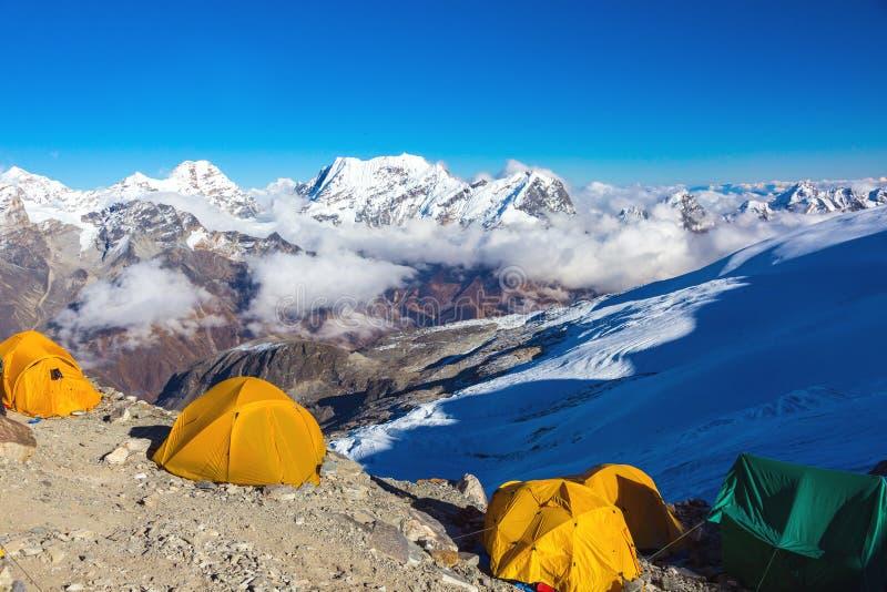 Acampamento da alta altitude de cimeiras da expedição da montanha no horizonte imagens de stock