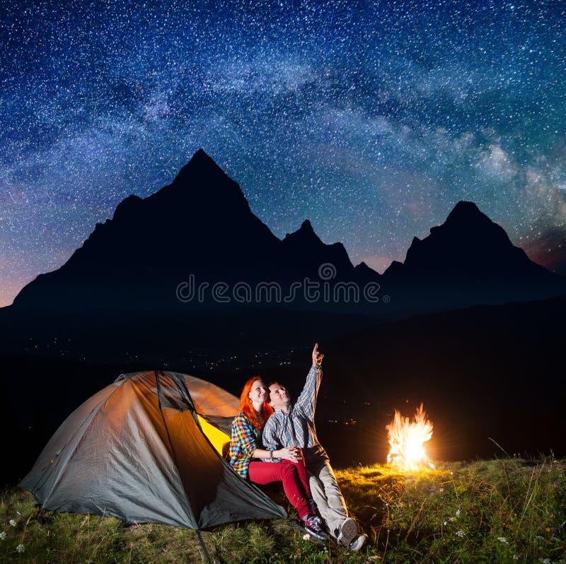 Acampamento da noite Turistas felizes dos pares que sentam-se perto da barraca e do fogo e que apreciam o céu estrelado incredibl fotografia de stock