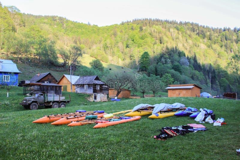Acampamento das ligas e dos caiaque da água que secam na grama na vila Carpathian no fundo das montanhas foto de stock