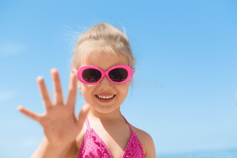 Acampamento de verão de ondulação da mão da praia da criança imagem de stock royalty free