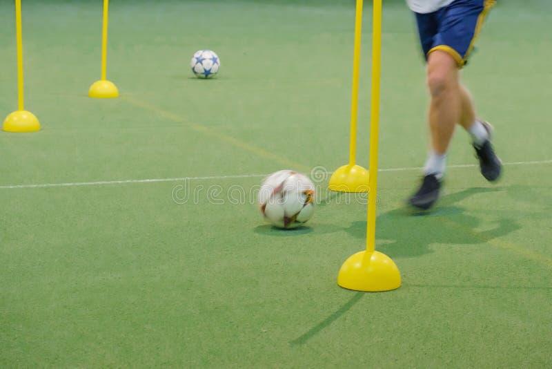 Acampamento do futebol para crianças Crianças que treinam habilidades do futebol com bolas e cones O slalom do futebol fura para  imagens de stock royalty free