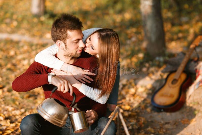 Acampamento do outono pares felizes que abraçam e que fazem o chá ou o café Aqueça bebidas fotografia de stock royalty free
