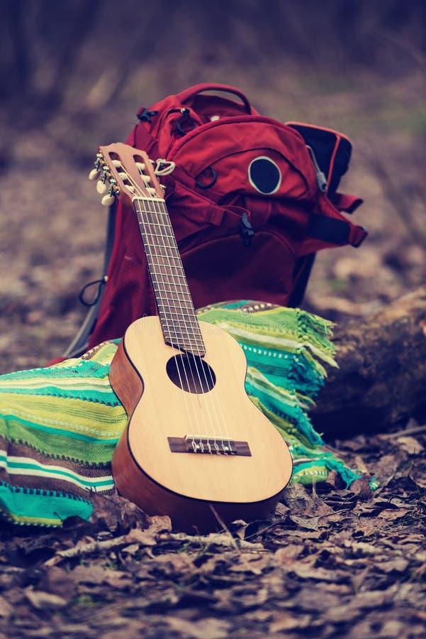 Acampamento em uma floresta - a guitarra pequena encontra-se em uma coberta ao lado do backp fotos de stock