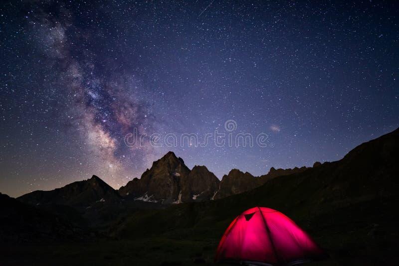 Acampamento sob o céu estrelado e Via Látea na alta altitude nos cumes Barraca iluminada no primeiro plano e no pico de montanha  foto de stock royalty free