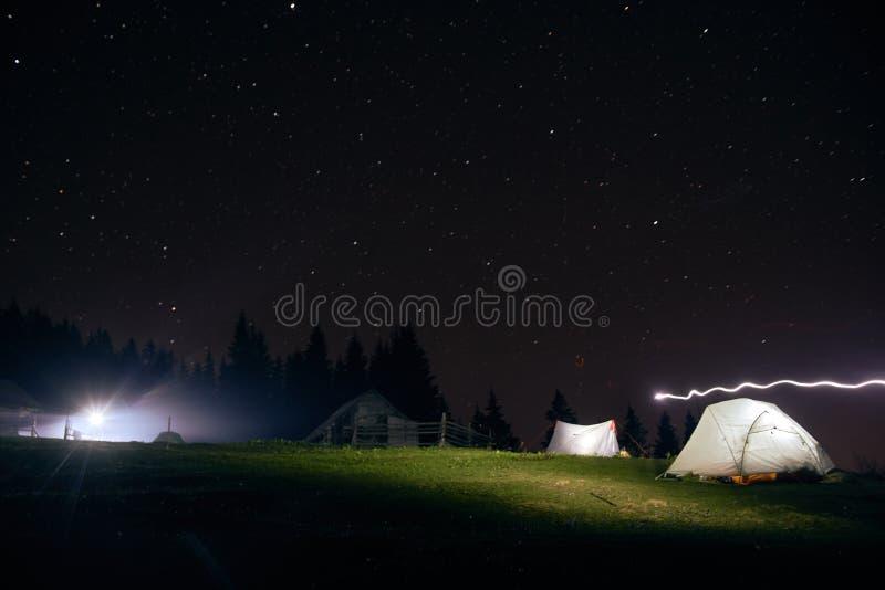 Acampando debajo de las estrellas en la noche en montañas, tiendas iluminadas fotografía de archivo